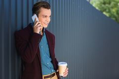 Smiling young man holding paper cup and talking. By smartphone royalty free stock photos