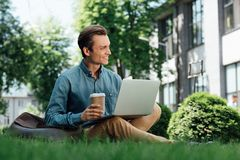 Smiling young man holding paper cup and using laptop while sitting. On grass royalty free stock photos