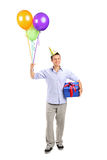 Smiling young man holding a present and baloons Stock Images