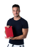 Smiling young man holding and showing book cover Stock Photo