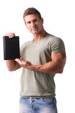 Smiling young man holding and showing book cover Royalty Free Stock Photo