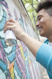 Smiling young man holding a spray can and spray painting on a wall outside Royalty Free Stock Photos