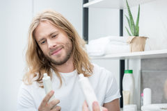 Smiling young man holding toothpaste while standing in bathroom Royalty Free Stock Photo