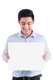 Smiling young man holding white sheet of paper Stock Photos