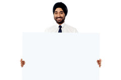 Smiling young man holding white sign board Stock Image