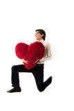 Smiling young man holds a  red heart Royalty Free Stock Photos