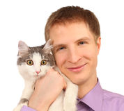 Smiling young man holds surprised cat isolated. On white background Royalty Free Stock Photo