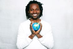 A smiling young man holds the world globe in his hands. A message of one love and peace Stock Photo