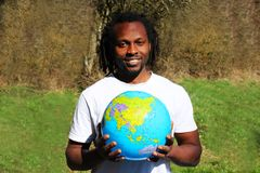 A smiling young man holds the world globe in his hands. A message of one love and peace Stock Photos