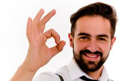 Smiling young man isolated on white background. Close up view of beardy male showing ok Royalty Free Stock Photos