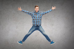 Smiling young man jumping in air Stock Photography
