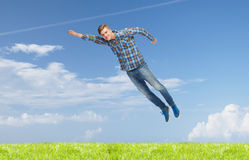 Smiling young man jumping in air Royalty Free Stock Image