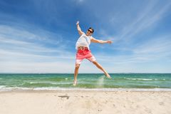 Smiling young man jumping on summer beach. Summer holidays and people concept - happy smiling young man jumping on beach Stock Photos