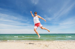 Smiling young man jumping on summer beach. Summer holidays and people concept - happy smiling young man jumping on beach Royalty Free Stock Photography