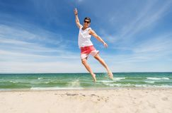 Smiling young man jumping on summer beach. Summer holidays and people concept - happy smiling young man jumping on beach Royalty Free Stock Photos