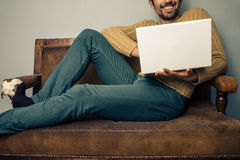 Smiling young man with laptop on old sofa Royalty Free Stock Photos