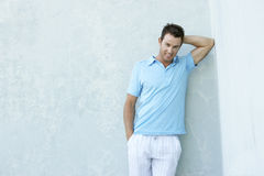 Smiling Young Man Leaning Against Wall Stock Images
