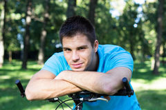 Smiling young man leaning on a bicycle Royalty Free Stock Photos