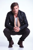 Smiling young man in leather jacket standing crouched Royalty Free Stock Images