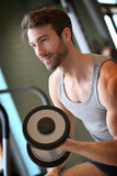 Smiling young man lifting weights in a fitness club Royalty Free Stock Photos