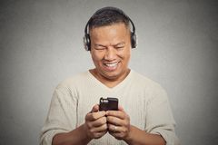 Smiling young man listening music on cell phone Stock Photos