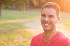 Smiling young man listening to music Stock Photos