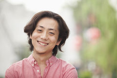 Smiling Young Man with Long Hair in Nanluoguxiang, Beijing, China Stock Photo