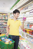 Smiling Young Man Looking At Food in Supermarket Stock Image