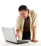 Smiling young man looking at laptop Royalty Free Stock Images