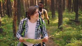 Smiling young man is looking at map and searching for right way in forest while multiethnic group of friends is