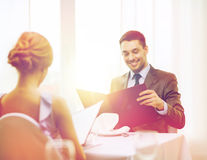Smiling young man looking at menu at restaurant. Restaurant, couple and holiday concept - smiling young men looking at menu at restaurant Royalty Free Stock Photography