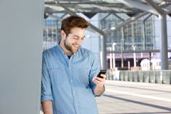 Smiling young man looking at mobile phone Royalty Free Stock Images