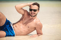 Smiling young man lying on the beach Stock Image