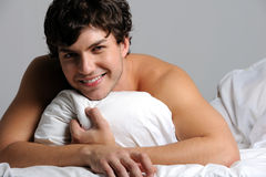 Smiling young man lying in bed. Portrait of a beautiful smiling young man lying in bed with pillow Royalty Free Stock Image