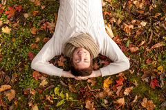 Smiling young man lying on ground in autumn park Stock Photos