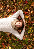Smiling young man lying on ground in autumn park Royalty Free Stock Image