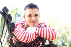 Smiling young man lying and resting on a bench Royalty Free Stock Photo