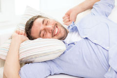 Smiling young man lying on sofa at home Royalty Free Stock Photos