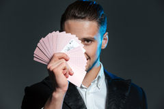 Smiling young man magician covered his face with playing cards Stock Photography