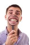Smiling young man through Magnifying glass Royalty Free Stock Photos