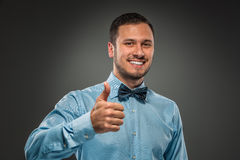 Smiling young man making the ok thumbs up hand sign Stock Photos