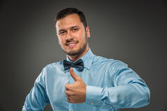 Smiling young man making the ok thumbs up hand sign Stock Photo