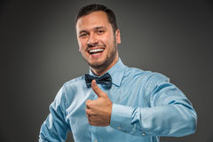 Smiling young man making the ok thumbs up hand sign Royalty Free Stock Photo