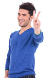 Smiling young man making the victory sign Royalty Free Stock Image