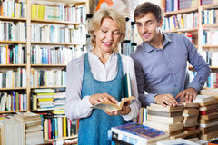 Smiling young man and mature woman holding books. Smiling friendly men and happy positive mature women holding books in hands in book store Royalty Free Stock Image