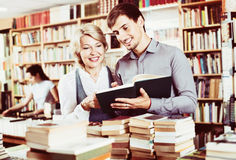 Smiling young man and mature woman holding books. Smiling friendly young men and happy positive mature women holding books in hands in book store Royalty Free Stock Photography