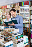 Smiling young man and mature woman holding books. Smiling friendly young men and happy  mature women holding books in hands in book store Royalty Free Stock Photos