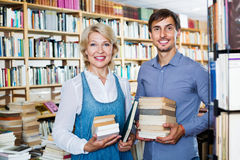 Smiling young man and mature woman holding books stock photo