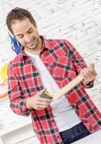 Smiling young man measuring wooden board Royalty Free Stock Photography