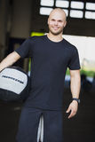 Smiling young man with med-ball at the fitness gym Royalty Free Stock Image